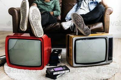 Two man sitting and two retro television