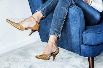Closeup pair of feminie legs on the sofa wearing heels