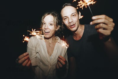Caucasian man and woman couple playing with sparklers celebration and festive party concept
