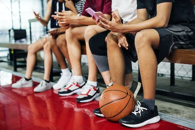 Group of young teenager friends on a basketball court relaxing using smartphone addiction concept
