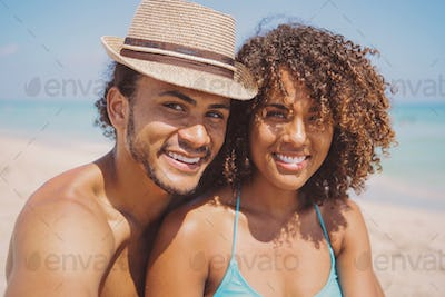 Couple looking at camera on beach