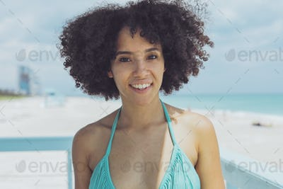 Cheerful black woman in sunlight on beach