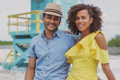 Cheerful ethnic couple looking at camera