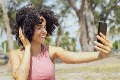 Laughing young girl taking selfie in park