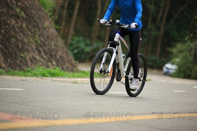 Riding mountain bike climbing slope on road