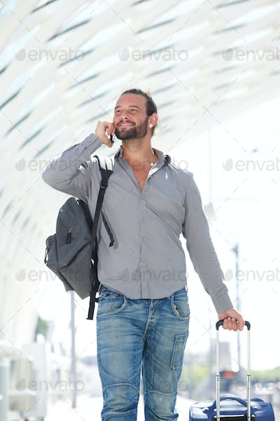 Handsome man walking with mobile phone and luggage