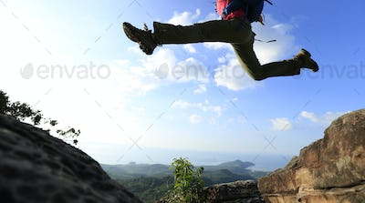 Jumping over precipice between two rocky mountains