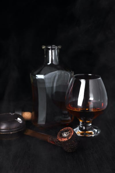Glass of whiskey with smoking cigar.