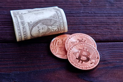 Dollar banknotes and Bitcoins on a wooden table