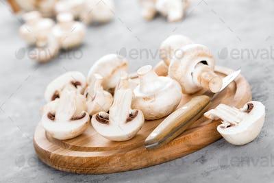 Fresh mushrooms. Raw mushrooms on wooden board. Champignons
