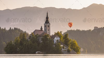 Island with church in lake Bled with orange hot air balloon