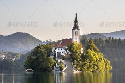 Island with church in lake Bled in hazy morning light