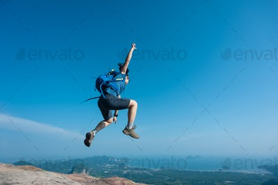Successful hiker jumping on mountain top cliff edge