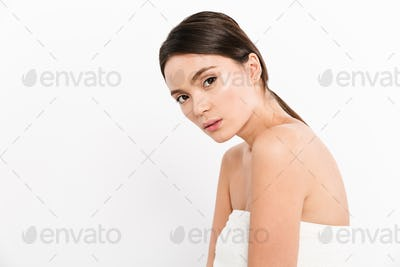 Young woman in towel looking camera isolated over white