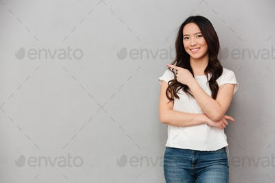 Photo of asian affable woman in casual t-shirt and jeans posing