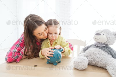 Mother and her child daughter putting coin to piggy bank