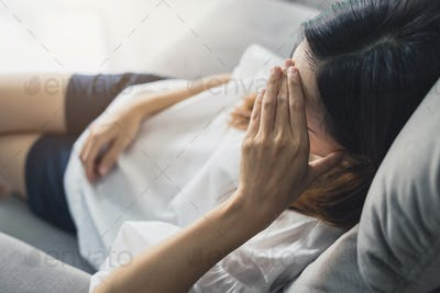 Depressed young woman holding hand on head