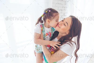 Little girl kissing her young mother