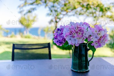 bouquet of pink and purple flowers in a vase on the table in the garden