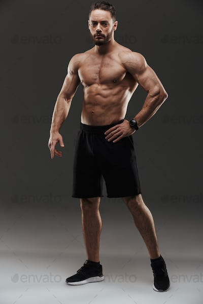 Full length portrait of a serious muscular man posing