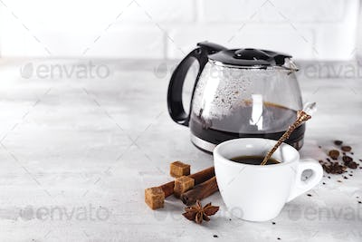 cup of hot coffee with glass teapot for breakfast.