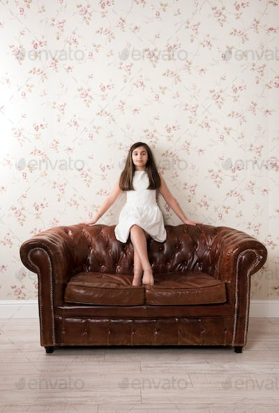 Portrait of a pretty little girl on a leather sofa