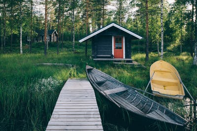 Traditional wooden hut. Finnish sauna on the lake and pier with fishing boats