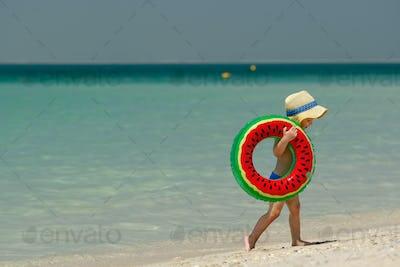 Toddler boy with swim ring on beach