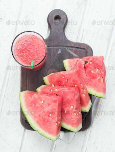 overhead shot of glass of juice and watermelon cut into pieces white wooden board