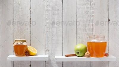 glass jar of honey on wooden shelf
