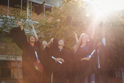 Successful graduate school kids throwing mortarboard in air in campus