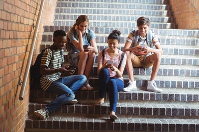 Classmates sitting on staircase and using mobile phone