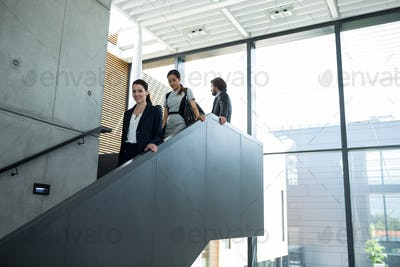 Confident businesswoman with colleagues climbing down the stairs