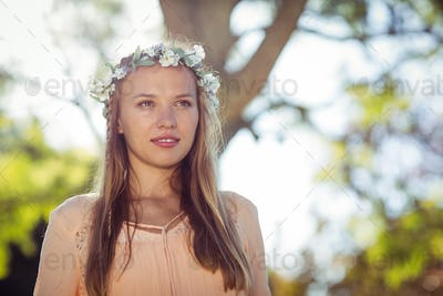 Beautiful woman with flower wreath standing in park