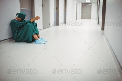 Tensed female surgeon sitting in corridor