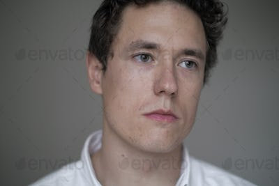 clean portrait of a serious caucasian man wearing a white shirt on a grey background