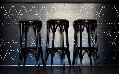 Bar counter with high chairs in empty modern restaurant
