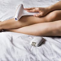 woman removing hair with special equipment at home on a bed