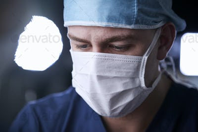 Male surgeon looking down, head and shoulders
