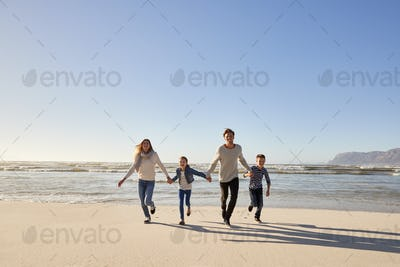 Family On Winter Beach Holding Hands And Running Towards Camera