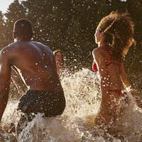 Young adult friends on vacation splashing in a lake