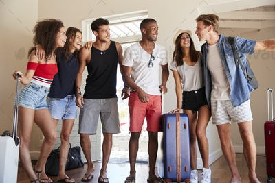 Group Of Friends Arriving At Summer Vacation Rental
