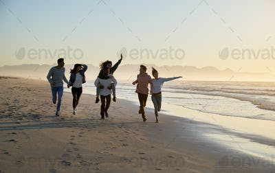 Group Of Friends Having Fun Running Along Winter Beach Together