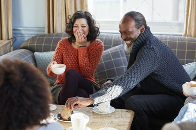 Middle Aged Couple Meeting Friends Around Table In Coffee Shop