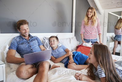 Family In Bedroom Pack Suitcases For Vacation And Use Laptop