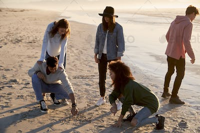 Friends Playing Noughts And Crosses In Sand On Winter Beach