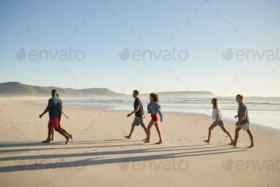 Group Of Friends On Vacation Walking Along Beach Together
