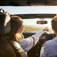 Young adult couple driving, woman pointing out directions