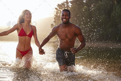 Young mixed race couple having fun in a lake