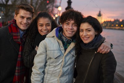 Portrait Of Friends Walking Along South Bank On Visit To London